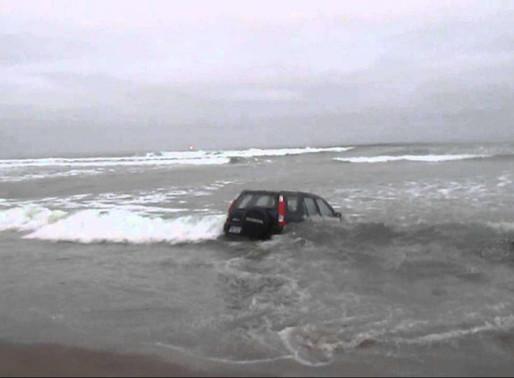 Il stationne sa voiture sur la plage à marée basse...