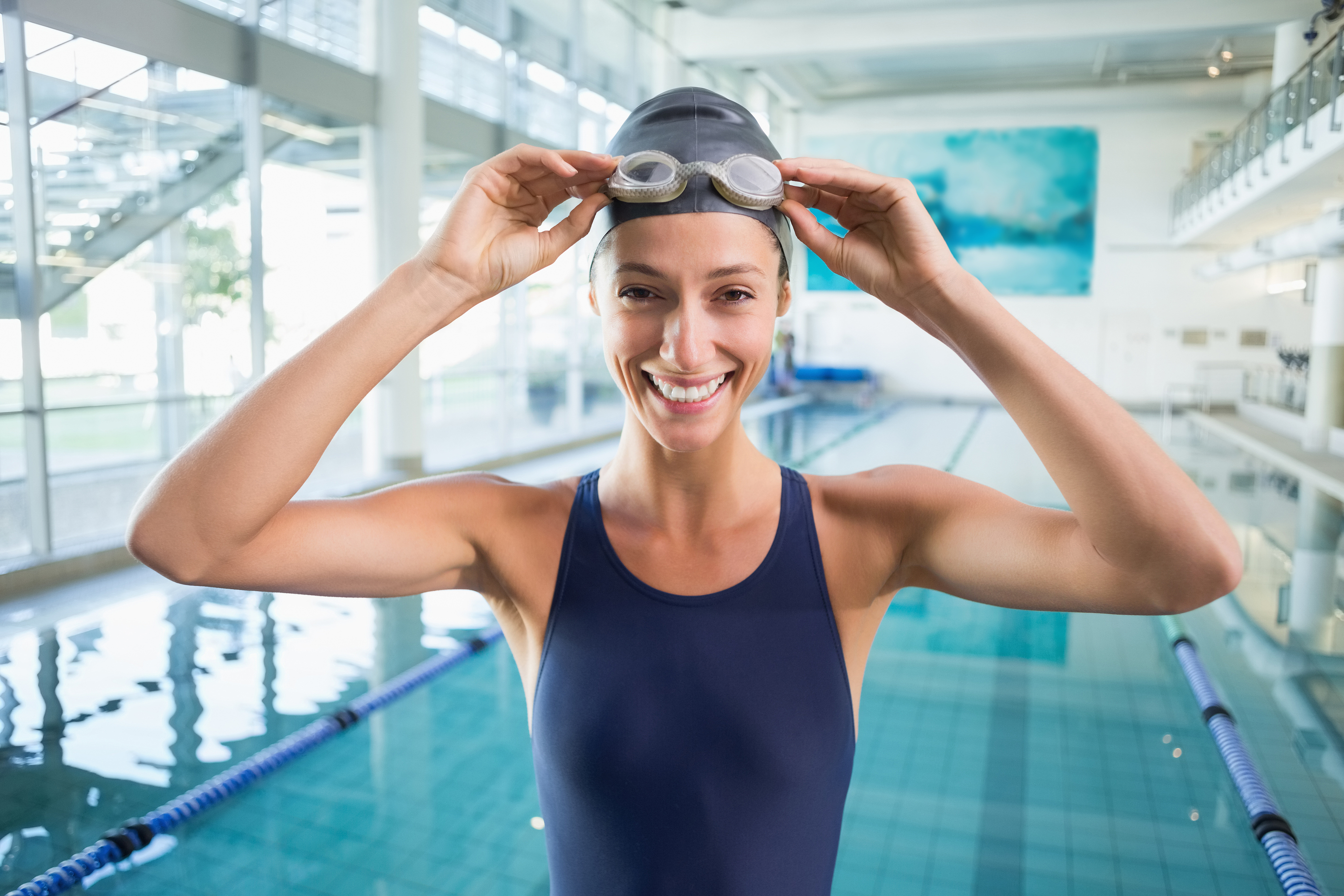 Pretty swimmer standing by the pool smiling at camera at the leisure center.jpg