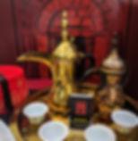 Arabische Kaffeegläser und Kaffeekanne, mit der ein traditioneller Kardamon-Kaffee als kleiner Schluck eingeschenkt wird.