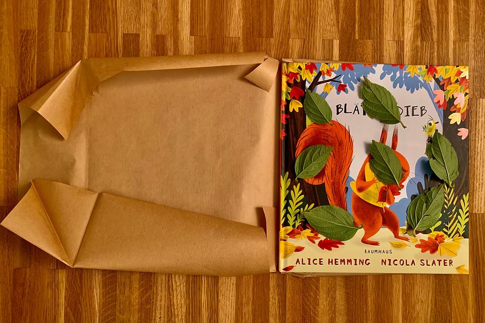 Blätter mit der linken Seite nach oben auf das Cover und die Rückseite legen. Das Buch mit Packpapier einpacken.