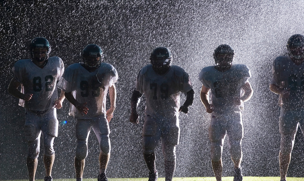 five football players in uniform, backlit so you can't see faces, with rain spraying down on them and a light shining from behind