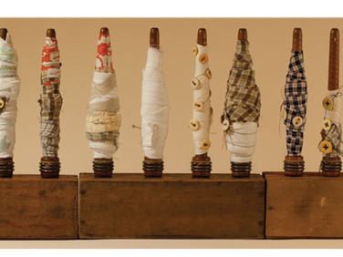 """WRAPPED IN MANY STORIES ONE 2012 27.5"""" x 10"""" x 3"""" —Found objects, wood, fabric, and buttons."""