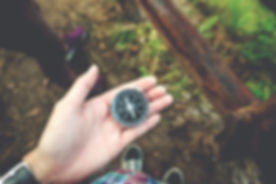Traveler man holding a compass on Mountain