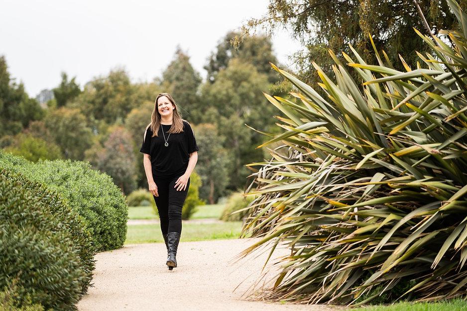 Trinette Jaeschke wellness coach, walking in grass feeling happy.