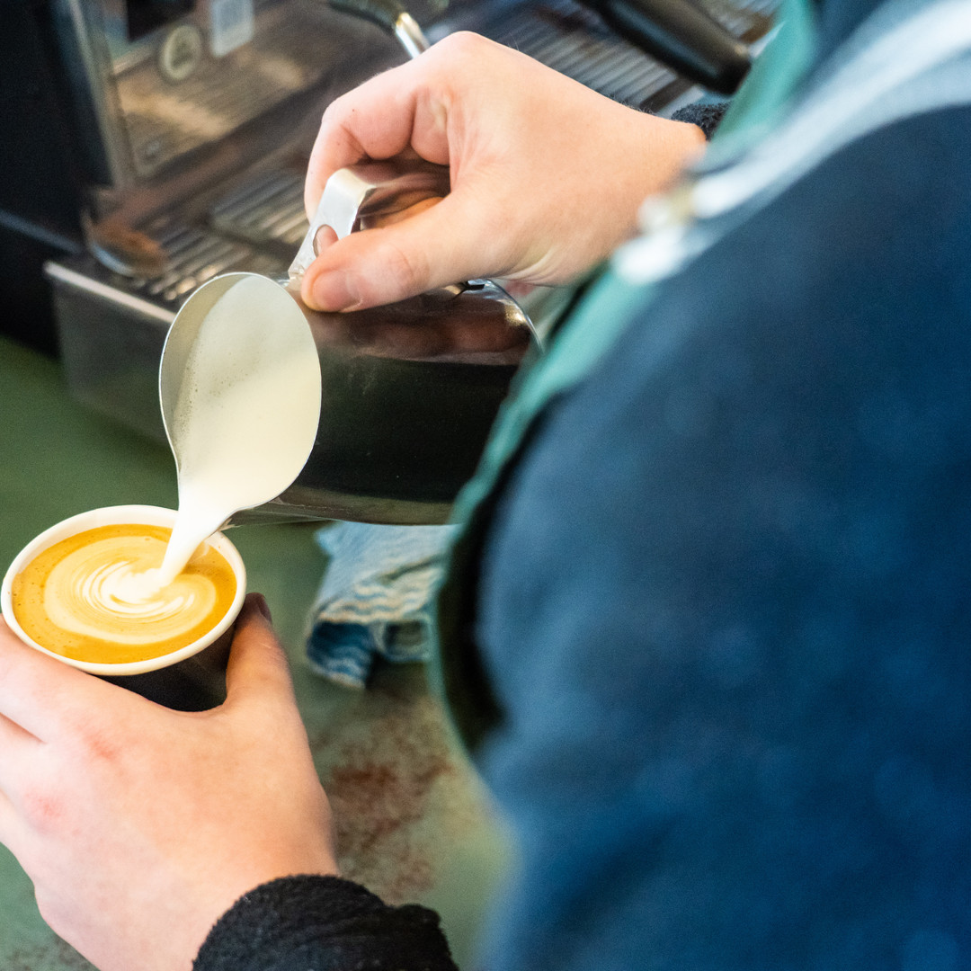 Mount Macedon Trading Post Cafe staff member pouring a take away cup of coffee