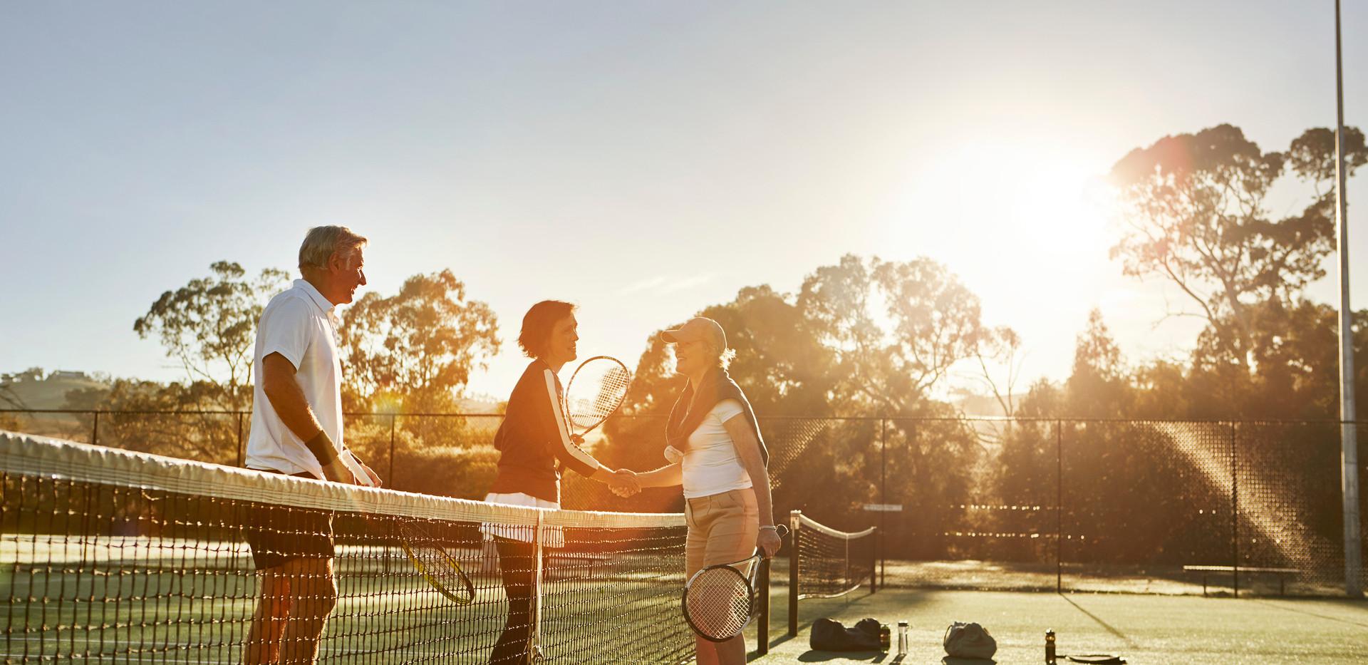 residents enjoying a game of tennis during sunset at the premium facilities at La Dimora Retirement Village