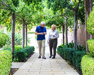 Residents enjoying a walk in the spacious manicured gardens at Rylands retirement village in East Melbourne
