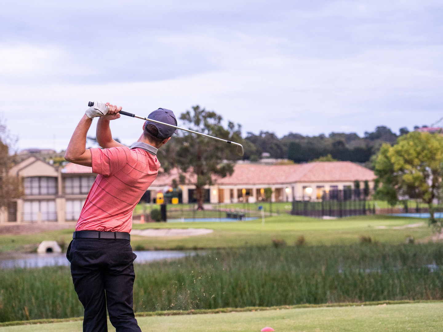 Golf member taking a swing over the lake with the club house in the distance at Hidden Valley resort 45 minutes from Melbourne