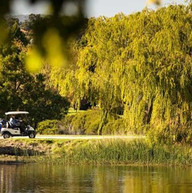 View over the lake of a golf buggy at Hidden Valley resort country club just 45 minutes north of Melbourne