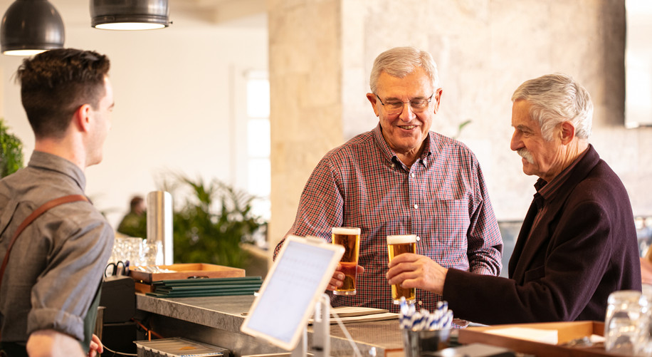 Residents from La Dimora Retirement at the bar in the grove ordering a beer
