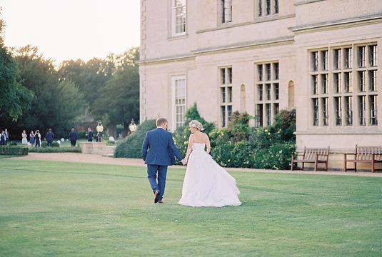 Bride & Groom walking across the beautiful lawn of Stapleford Park in the Midlands, UK.
