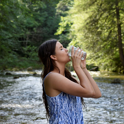 Canva - Woman Drinking Water by the Rive