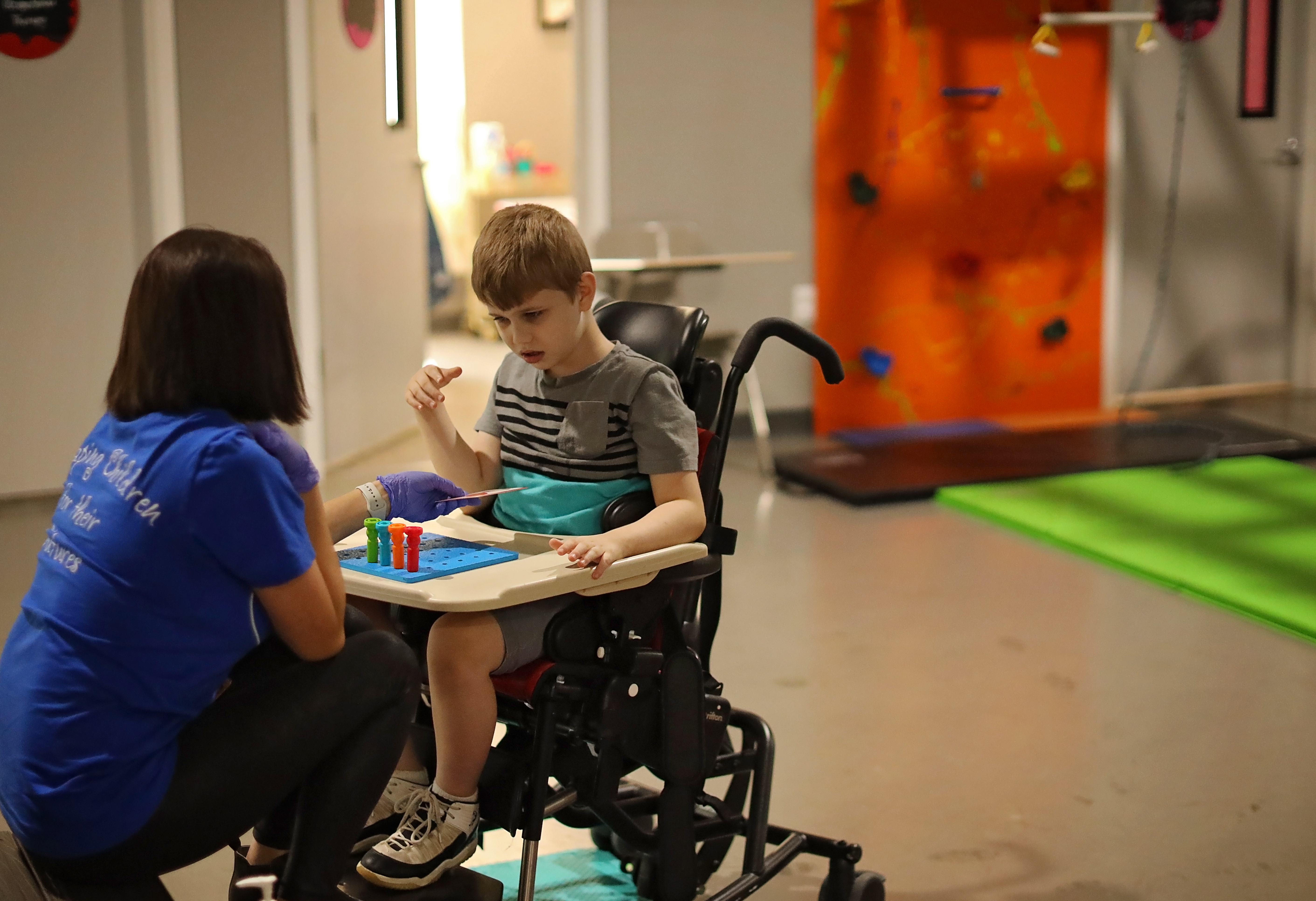 boy in wheel chair doing therapy