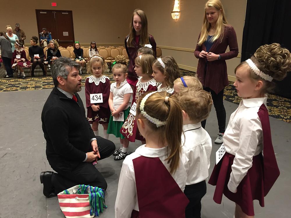 Adjudicator Jim Mueller congratulates his line of First Feis dancers