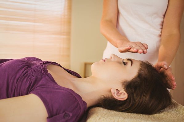 Young woman having a reiki treatment in