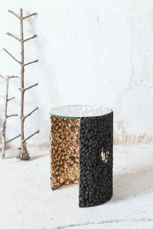 Side table / Ø38x44 cm  A matter surface envelopes and protects the inside of the table. A dialogue between the impurity of the dross and the brilliance of the bronze.   Polished bronze, dross and extra-clear crystal. Limited edition