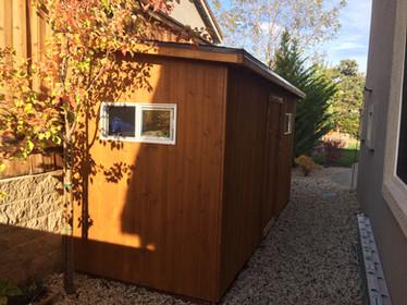 Custom backyard shed with wood siding and trim
