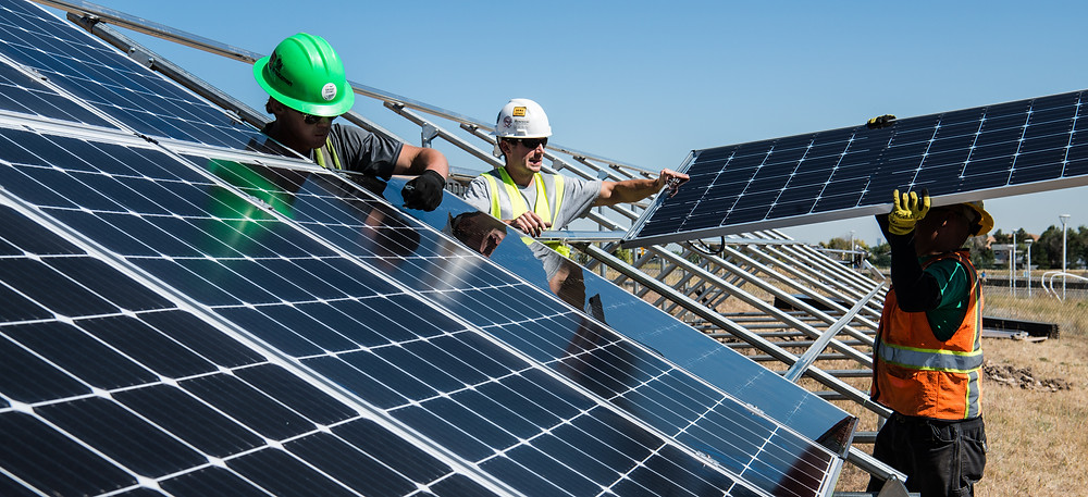 solar panels being installed by three workers