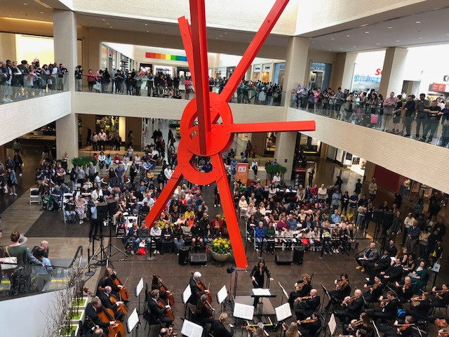 Crowds are seated and line upper level railings to listen to The Dallas Opera orchestra perform at the NorthPark Center