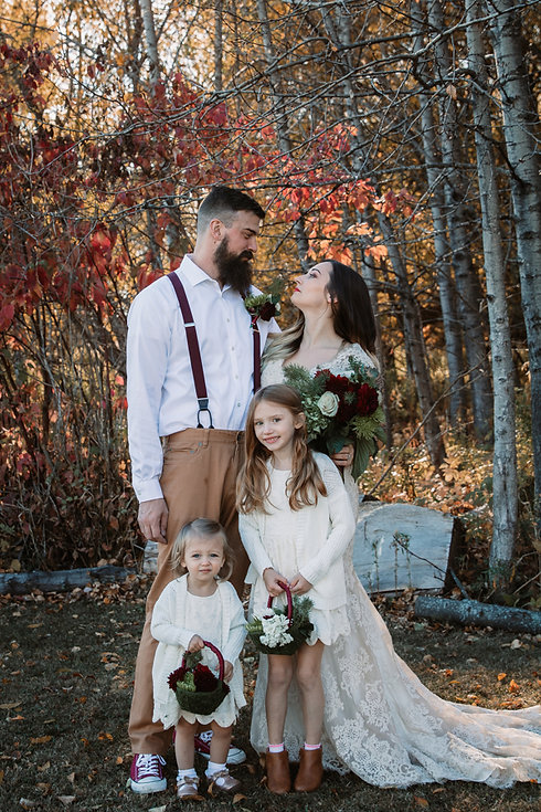 a bride and groom family picture with two daughters flower girls with a fall wedding