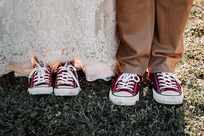 bride and groom wearing matching maroon Chuck Taylor Converse