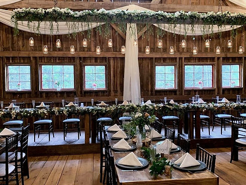 rustic wedding reception with black chairs and wood tables.