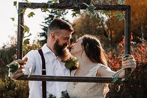 wedding couple holding frame lovingly gazing