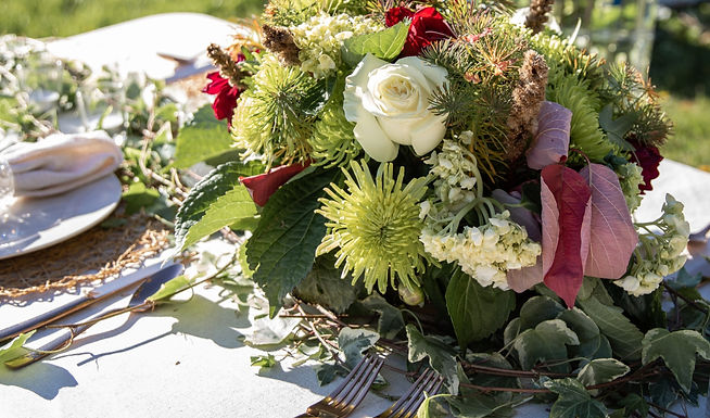 wedding flower arrangement with white roses, wildflowers, and green mums