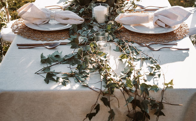 a wedding table arrangement laced with ivy, white candles.