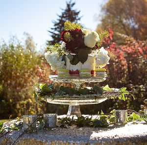 wedding cake with red and white frosting, green macaroons, with flowers on top