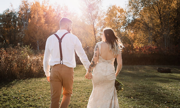 bride and groom walking hand in hand on their wedding in an autumn field