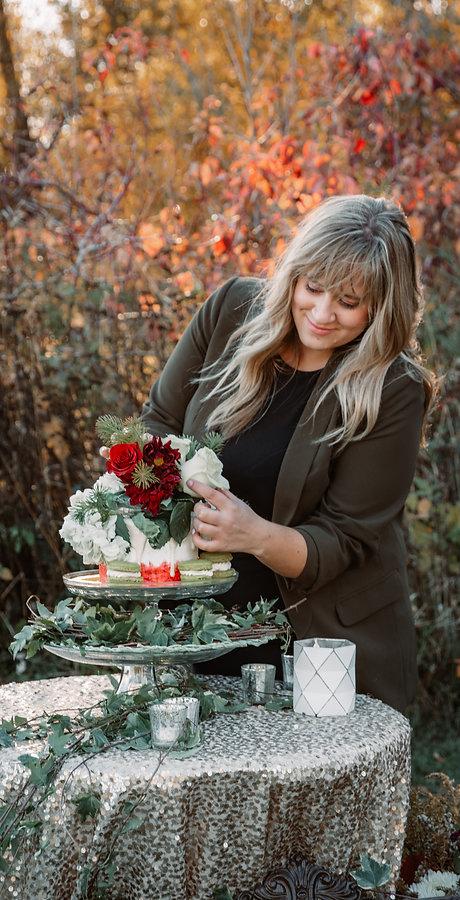 wedding planner adjusting flowers on top of a wedding cake