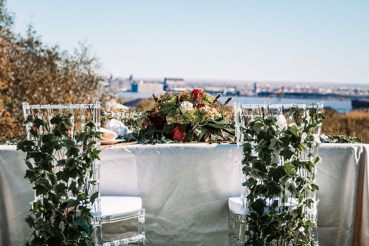 a wedding table arrangement with ivy adorned chairs and a view of Lake Superior