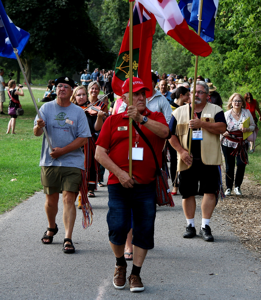 MNO Veterans' Council Senator Guy Mandeville leads the  procession following the arrival of voyageur canoes on the  shore of Beavermead Park in Peterborough on Aug. 16.