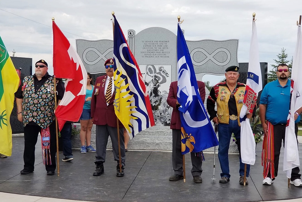 MNO Veterans' Council Chair Brian Black (far left) carried  the Canadian flag alongside veterans from across the  Métis Homeland during a procession leading to the  National Métis Veterans' Memorial Monument in Batoche.