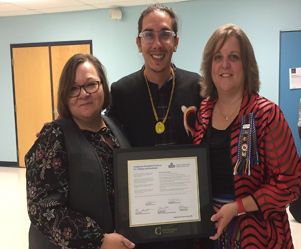 MNO Vice-Chair Sharron Cadeau, Conestoga College  Indigenous Studies Coordinator Andrew Judge and MNO  Grand River Métis Council President Jennifer Parkinson  celebrate Conestoga College's historic signing of the  national Indigenous Education Protocol on Oct. 31.