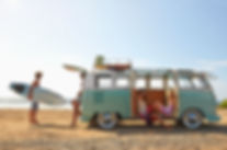 green and white VW van with 4 surfers hanging out