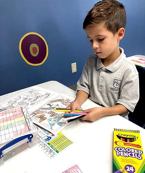 Kindergarten+boy+coloring+with+pencils.j