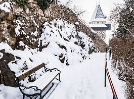 Snow covered bench and path to Uhrturm c