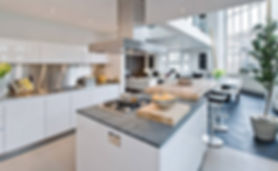 White kitchen island with stools in the Chelsea apartment by London interior designer Catherine Wilman