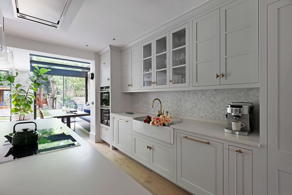 White open plan kitchen-diner with contemporary kitchen island and banquette seating by Catherine Wilman Interiors in Maida Vale, West London.