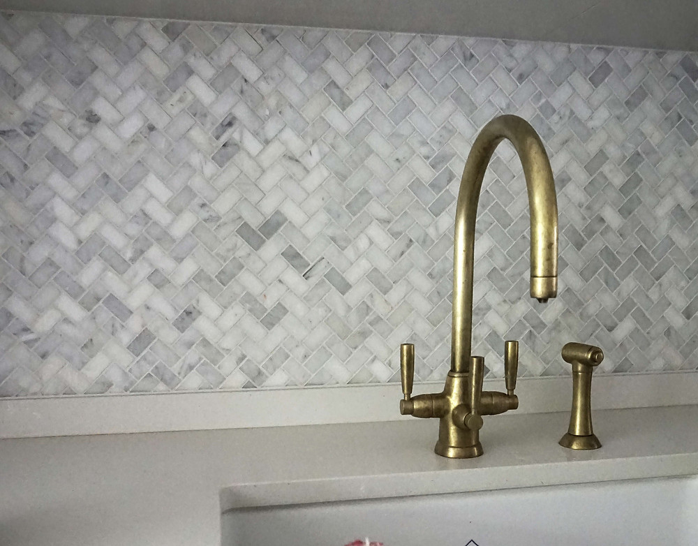 Herringbone mosaic tile pattern splashback and Perrin and Rowe brass kitchen taps with white quartz worktop in London kitchen design by Catherine Wilman