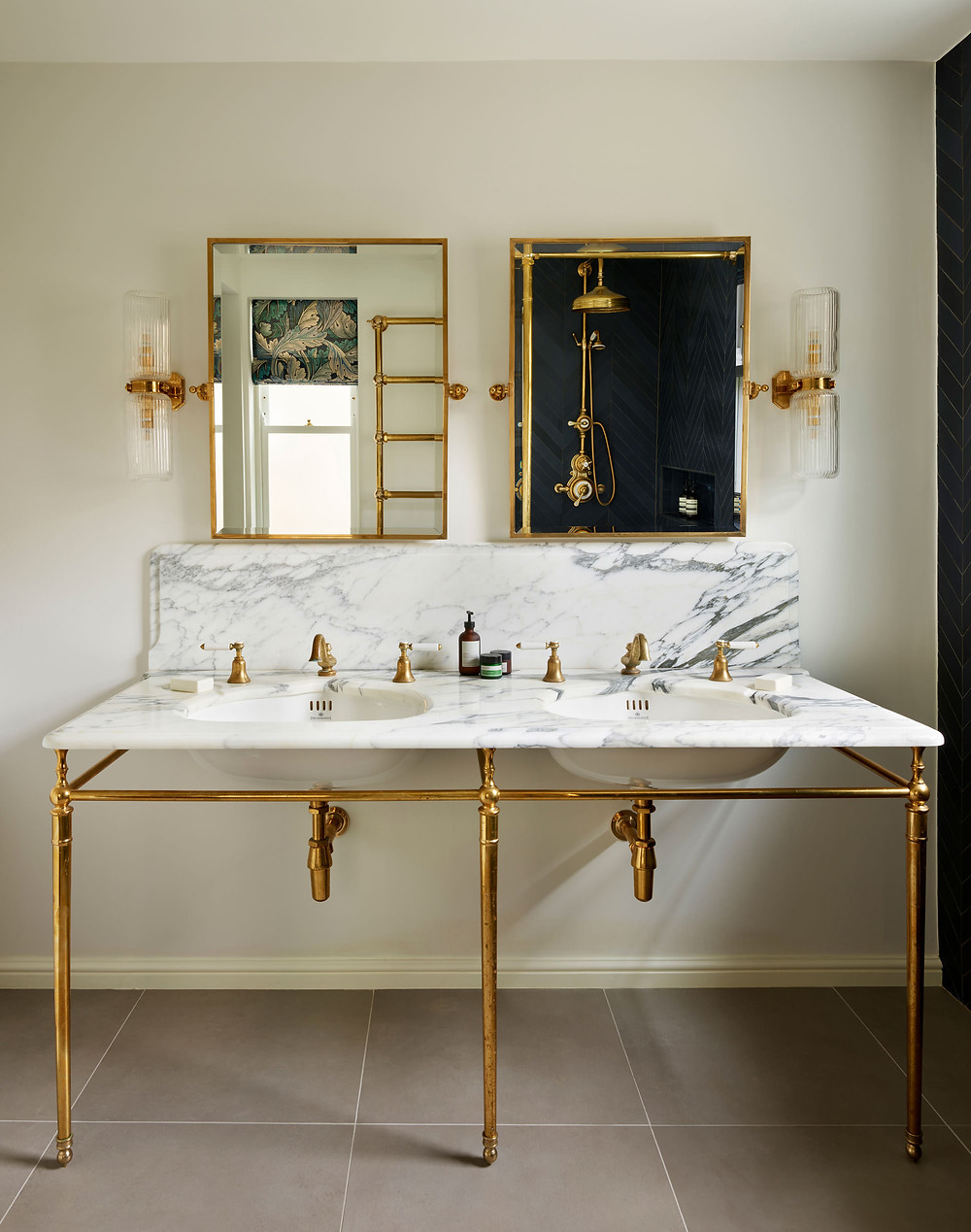 Luxury interiors, double marble vanity with large brass-framed tilt mirrors