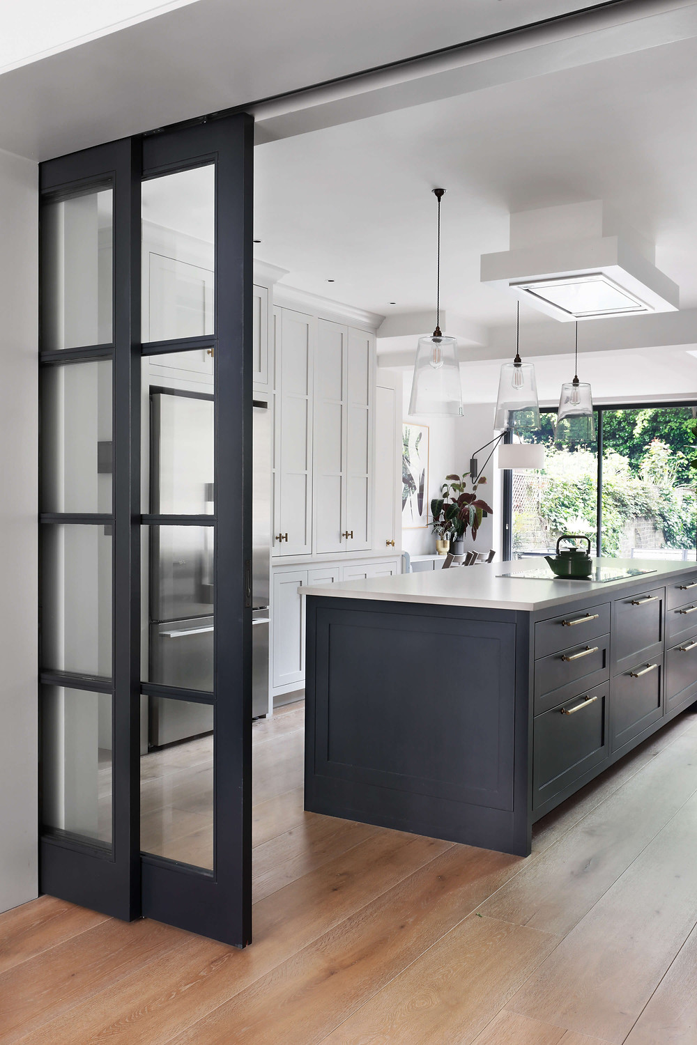 bespoke sliding door at the open plan kitchen in Maida Vale, West London, designed by Catherine Wilman