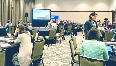 Diverse persone sedute per tavoli durante un workshop sull'accessibilità