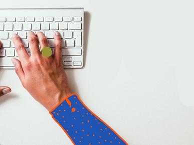Una tastiera e una mano che scrive