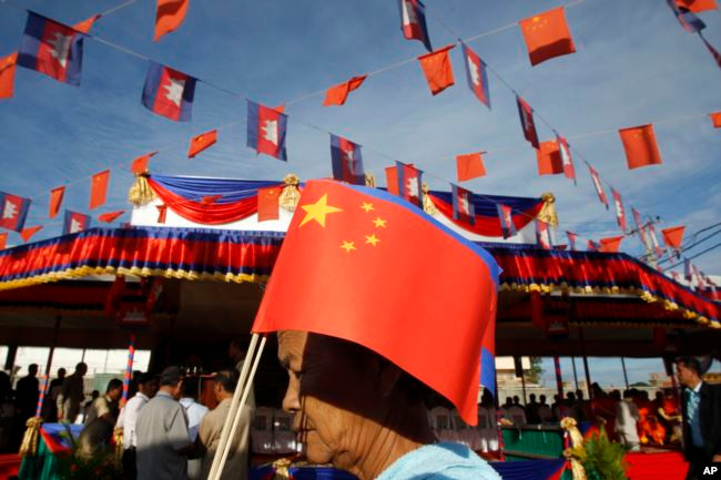 Une Cambodgienne tient un drapeau chinois à Takhmao