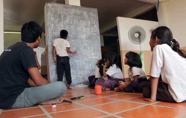 Les enfants attendent avec impatience leur tour pour lire à haute voix l'alphabet anglais lors d'un cours