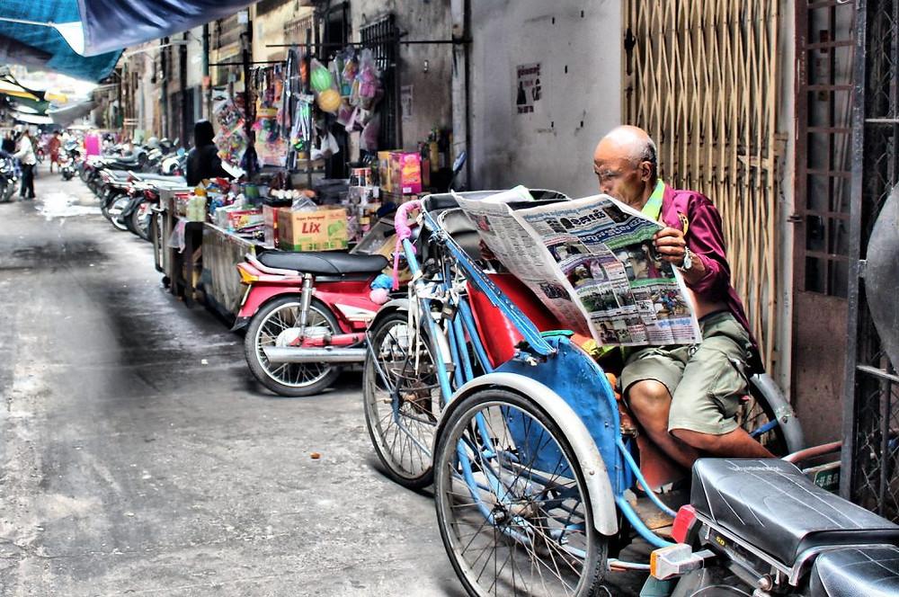 Pause lecture pour le conducteur de cyclo-pousse