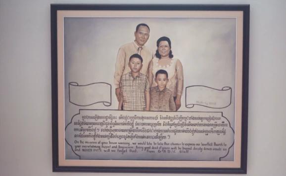 Un tableau représentant la famille de Ros Sopheap, cadeau de ses collègues du GADC, est exposé sur un mur le long de l'escalier de sa maison. (Khan Sokummono/VOA Khmer)